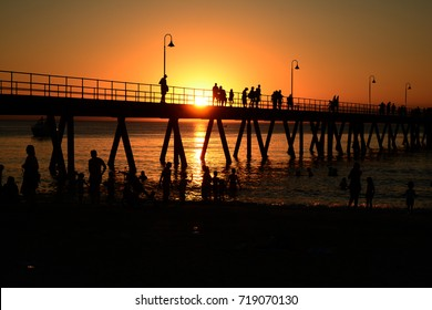 people shown in silhouette swimming in the beach at sunset in South Australia