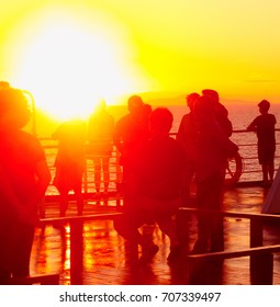 people at the side of the ship are standing and watching the sunset in the ocean