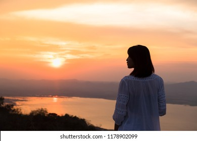People side view,photographer woman take photo with old camera.Asian traveler female sightseeing with mirrorless camera against sunset background. Travel and Photographer concept.