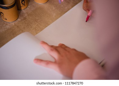 People sign a wedding guestbook with a pen.