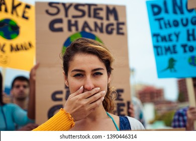"People with signs demanding ""climate change"" Justice and Climate. Group of demonstrators fight for climate change. Symbol of woman silenced by politics  – Image"