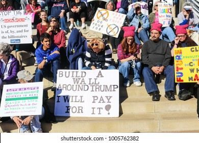 People with signs-some with pussy hats-sitting on steps at Womens March in Tulsa Oklahoma 2018