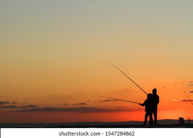 People silhouette fishing at sunset