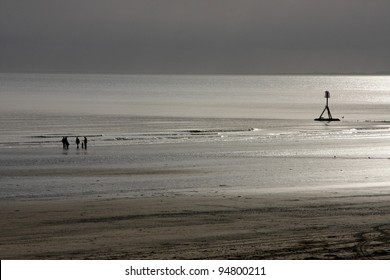 People in silhouette on sunlit beach at low tide.