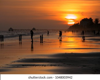 People silhouette at sunset on the beach at Fort Myers, Florida