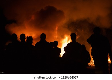 People silhouetted standing around a fire set off by illegal fireworks in California. A bush fire outside of a building.