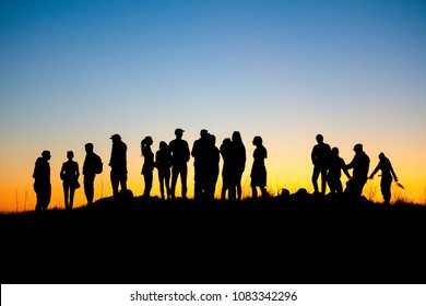 People silhouettes against the twilight sky