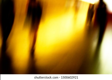 People silhouettes in blur. Moving people in yellow light. Passengers walking fast in a subway.