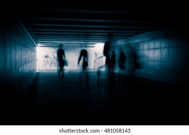People silhouettes in the dark urban tunnel.