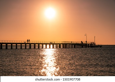 People silhouettes enjoying the sunset over ocean on a wooden pier