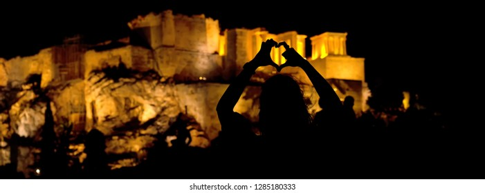 People silhouettes in the foreground, with Acropolis night view at the background, Athens, Greece