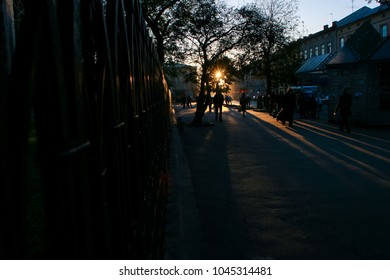 people silhouettes on dark old city street at back-light of sun through trees at sunset in european city Lvov