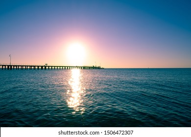 People silhouettes on long wooden pier at sunset