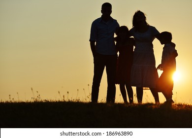 People silhouettes on summer sunset meadow