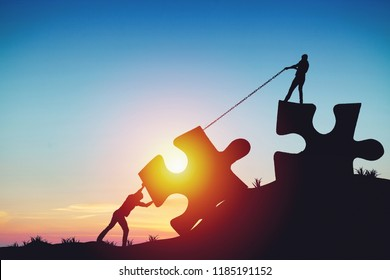 People silhouettes putting puzzle pieces together on sunlight background. Business idea concept