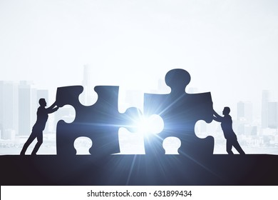 People silhouettes putting puzzle pieces together on abstract city background with sunlight. Team work concept