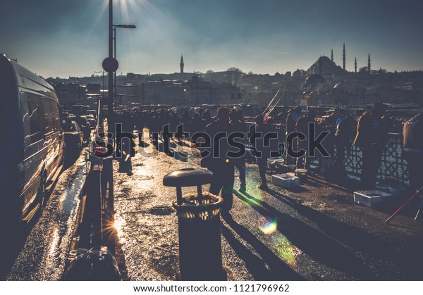 People silhouettes walking on Galata Bridge in Istanbul, Turkey. Urban view with traffic jam and locals.