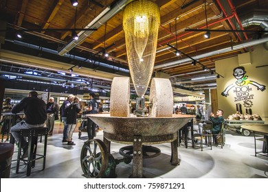 people sit beside a big millstones mill inside a modern restaurant in Fico Eataly World in Bologna, Italy, 19 Nov 2017