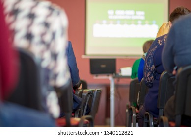 People sit at a business seminar. Back view. Shallow depth of field