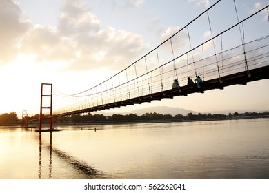 People Sit On The Bridge With The Sun Shining, Summer warm evening and a beautiful sunset in nature.
