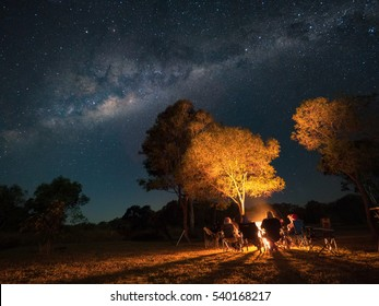 People sitting around a camp fire under the milky way