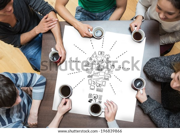 People sitting around table drinking coffee with page showing idea and innovation graphic