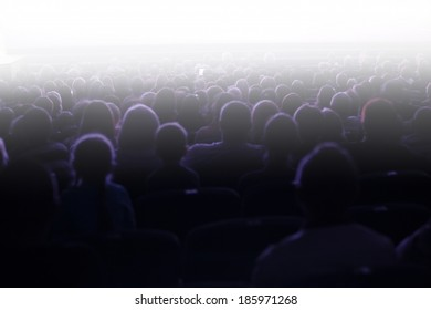 People sitting in an audience facing towards a bright light with flare effect at a live performance or cinema