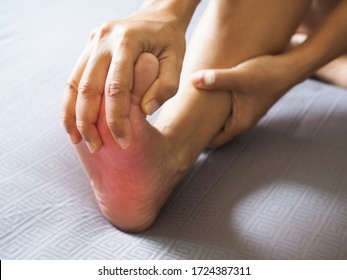 People sitting in bed with foot pain use hand to massage toe, leg, ankle and soles to relax and relieve pain.