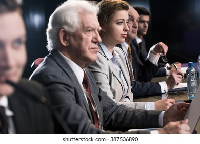 People sitting beside long table during science conference