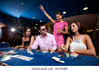 people sitting in a casino, playing poker, man with glasses winning