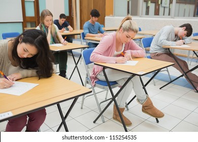 People sitting at the classroom and writing writing
