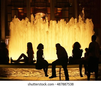 People sitting at the fountain at Lincoln Center, NYC, at night