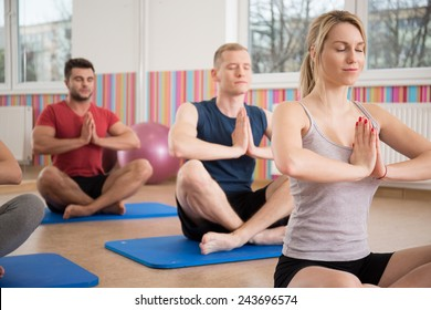 People sitting in lotus position during yoga class