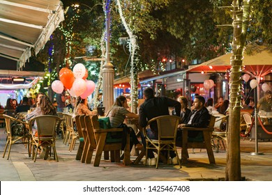 People sitting for meal in a Street of a new city of jerusalem in israel palestine