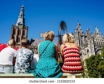 People sitting on benches and enjoying the view on the St. John's cathedral in 's-Hertogenbosch, Netherlands, during the Boulevard street theater