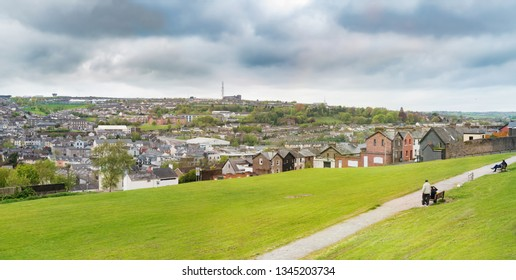 People sitting on the benches and looking at the panorama of Cork city in  spring. Ireland.