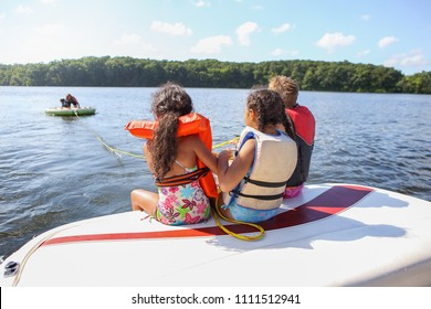 People sitting on a boat and tubing on an inland lake