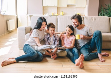 People are sitting on the floor. Boy has book. He reads it with sister and mom. Guy has a cup and look at book. He smiles.
