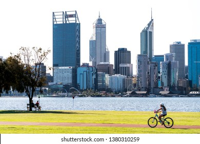 People sitting on park bench and cycling girl at Sir James Mitchell Park in South Perth, with the Swan River and Perth City skyline in shot. PERTH, WESTERN AUSTRALIA. April 25, 2019.