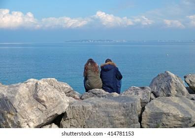 people sitting on the rocks watching the horizon