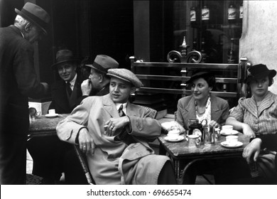 People sitting outdoors at sidewalk cafe tables