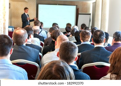 people sitting rear at the business conference and the speaker at the screen