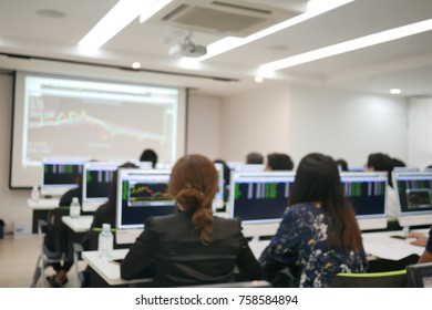 people sitting in training room looking at personal computer with numbers and graphs on the screen. Blur background and concept.