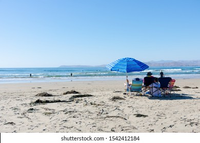 People sitting under bright blue striped umbrella at the beaching looking at the ocean