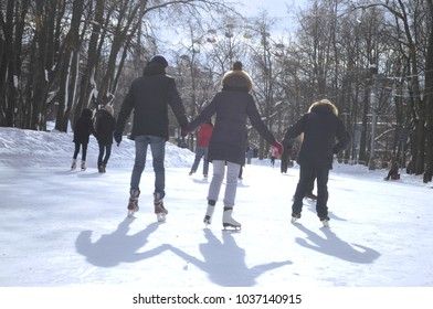 People skating at ice rink in the park.