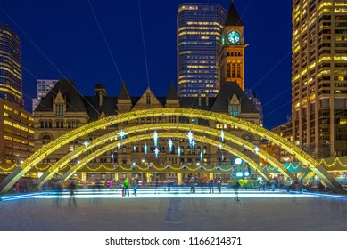People skating in Nathan Phillips square at night.  The Toronto famous place is a major tourist attraction in Canada