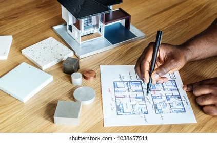 People sketching house plan blueprint