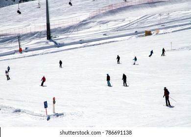 People skiing downhill on a piste in Gargellen, Austria