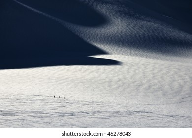 People skiing on glacier in La Grave with strong shadows painting in the field of snow