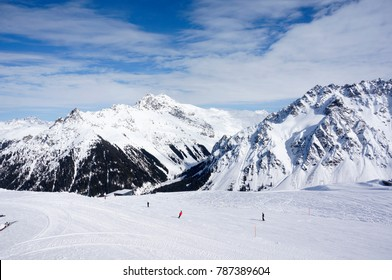 People skiing on the lovely empty slopes in Austria's Montafon ski resort with beautiful mountain peaks background